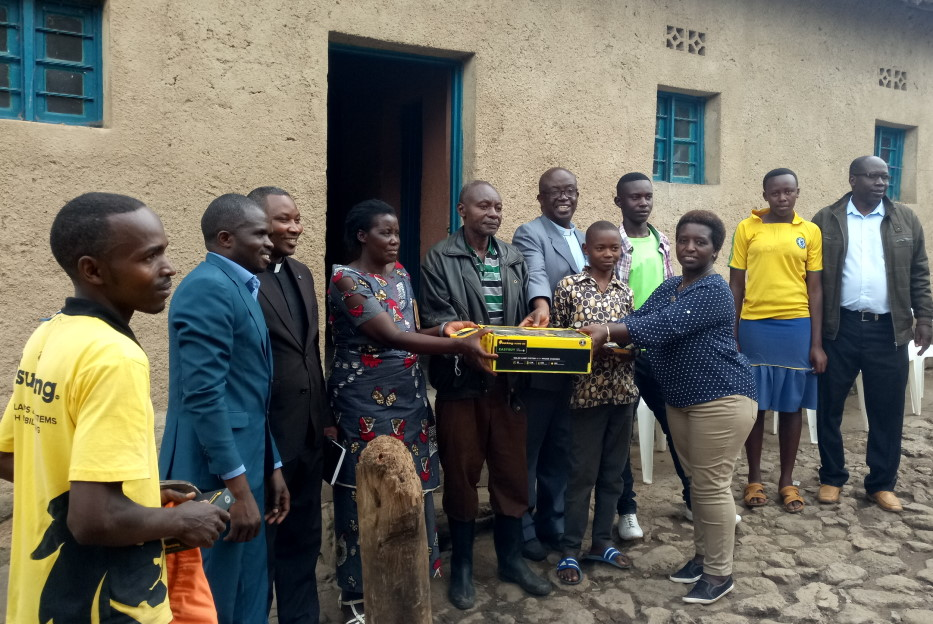 The mayor handing over a SHS kit to the first family of Mr Laurent Murindabigwi in Kamonyi village